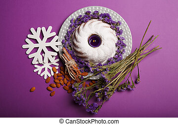 vista superior, de, um, prato, com, um, anel, bolo, um, vela, amêndoa, canela, snowflakes, ramos, de, flores, ligado, um, violeta, experiência.