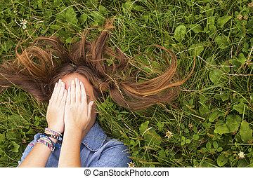 vista superior, menina jovem, mentir grama, olhos cobre, com, hands.