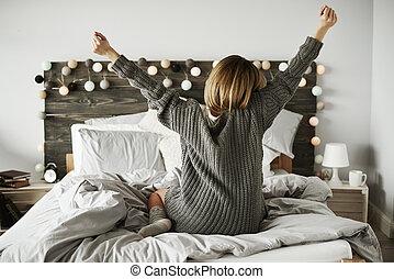 vista trasera, de, mujer se estirar, en, ella, cama