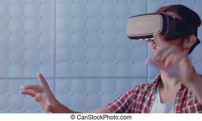 Visualized futuristic world wearing virtual reality headset trying to adjust reality. Man touch virtual wall using modern vr glasses indoors. Modern technologies. Prores 422.