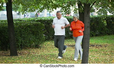 Vital motion - Couple of elderly people jogging in the park ...