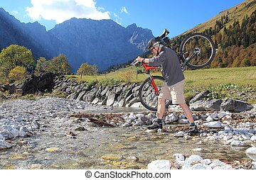 Vital Senior shouldering a Mountainbike river crossing