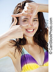 vitality - young woman on the beach, making frame with her ...