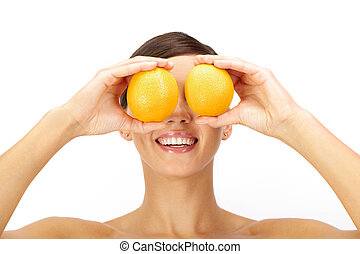 Vitamin C - A young woman holding two oranges