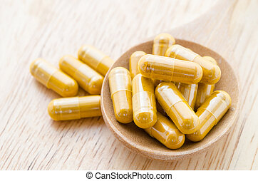 Vitamin capsules in a wooden spoon.