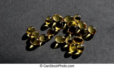 Vitamin D capsules pour on top on a black background. Health support and treatment. Biologically active additives.