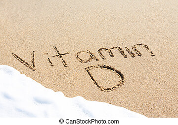 Vitamin D written in the sand with foam from a wave washing...