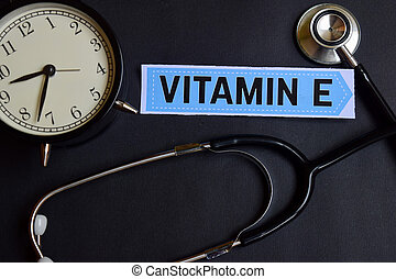 Vitamin E on the paper with Healthcare Concept Inspiration. alarm clock, Black stethoscope.