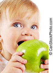 Portrait of happy small girl eating ripe apple