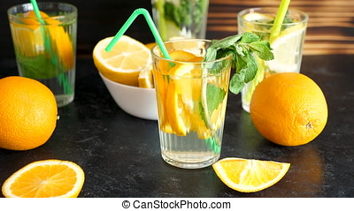 Vitamin water with slices of oranges and mint on a wooden...
