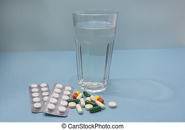 Vitamins and pills on blue background. Glass of water for taking medicine. Side view, close-up, selective focus