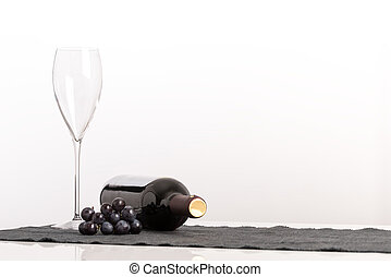 Viticulture and wine concept with an elegant empty wineglass alongside a bunch of black grapes and unlabeled bottle of red wine on its side against a white background with copyspace for your advert.