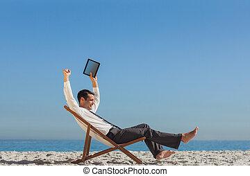 vitorioso, jovem, homem negócios, praia, descansar, seu, cadeira convés, segurando, seu, tabuleta