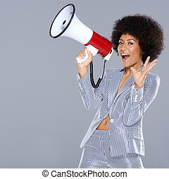 Vivacious beautiful African American woman holding a megaphone in her hand gesturing at the camera with an excited animated expression