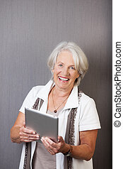 Vivacious elderly woman with a tablet-pc