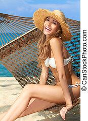 Vivacious happy woman in bikini on hammock