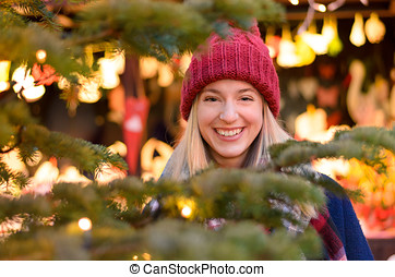 Vivacious happy young woman at a Christmas market or outdoor...