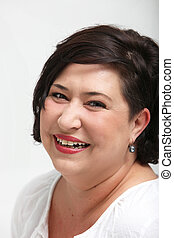 Vivacious laughing overweight woman smiling spontaneously as...