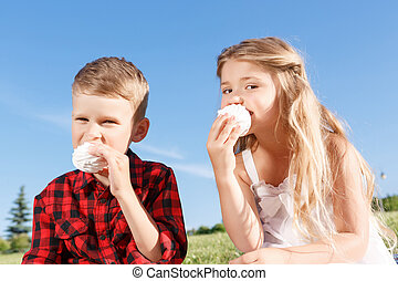 Vivacious little boy and girl eating marshmallow