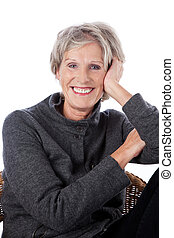 Relaxed vivacious older woman with a lovely friendly smile sitting in a wicker chair isolated on white