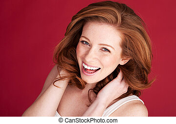 Vivacious redhead woman laughing looking up in to the camera, studio on red.