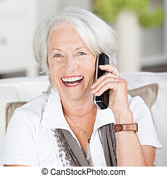 Vivacious attractive grey haired senior woman chatting on her mobile laughing as she shares a joke with the caller