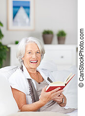 Vivacious senior woman reading a book sitting comfortably on a couch in her living room