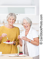 Two vivacious senior women enjoying cake for tea standing together in the kitchen chatting and relaxing