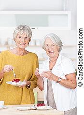Vivacious senior women enjoying cake for tea - Two vivacious...