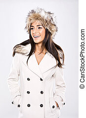 A beautiful laughing vivacious lady dressed in winter coat and fur hat on white.