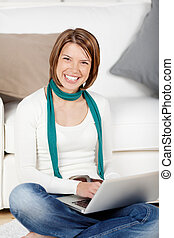 Vivacious woman using a laptop sitting on the floor in front...