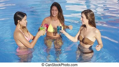 Vivacious women toasting with tropical cocktails - Vivacious...