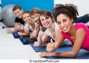 Vivacious young people working out in the gym together in...