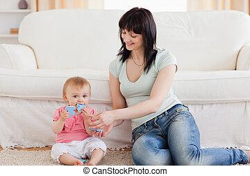 vivendo, atraente, dela, enquanto, sentando, bebê, segurando...