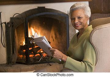 vivendo, mulher, sala, sentando, jornal, sorrindo, lareira