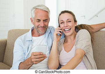 vivendo, par, lar, falando, sofá, seu, telefones, sala, sentando, texting, feliz