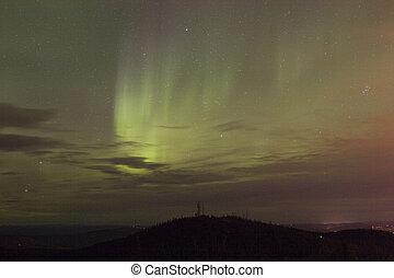 Vivid aurora borealis through clouds