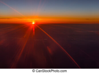 Vivid orange sunset or sunrise over the clouds