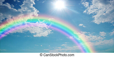 Wide blue sky with pretty clouds, a bright sun shining centre top and a large rainbow arcing from left to right with copy space