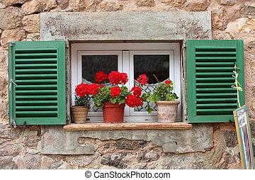 Vivid red geraniums on a windowsill
