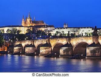 Vltava river, Charles Bridge and Prague Castle at night against a dark blue sky. Karluv Most, Prazsky hrad. Prague. Czech Republic