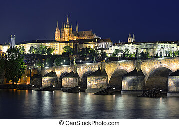 Vltava river, Charles Bridge and St. Vitus Cathedral at night against a dark blue sky. Karluv Most, Prazsky hrad. Prague. Czech Republic