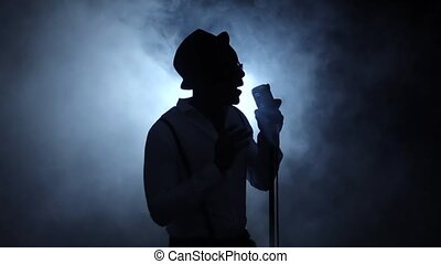 Vocalist half of the turnover in the smoke and white light singing at the microphone. Black background. Silhouette. Slow motion