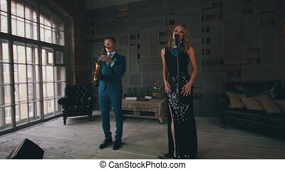 Vocalist in glowing dress perform on stage with saxophonist. Retro style. Jazz