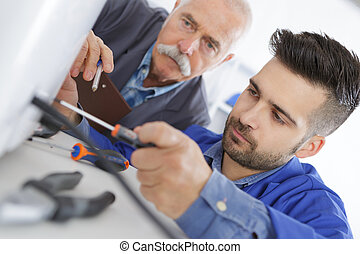 vocational student learns air conditioning repair from an ...