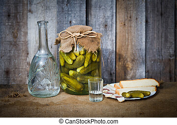 Vodka decanter, pickle and snack, image in the soft blue toning