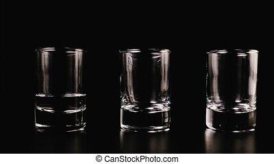 Vodka fills a glass on a black background. Stop motion,...