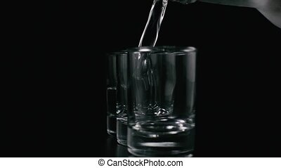 Vodka from a bottle pours into a shot. Slow motion - Iced...