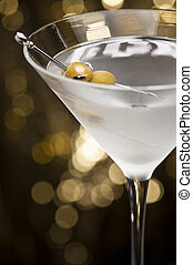 Vodka Martini with olive garnish in front of a gold glitter...