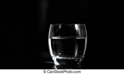 Vodka splashing in super slow motion against black...